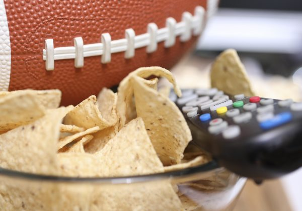 footbal next to a snack bowl and remote control