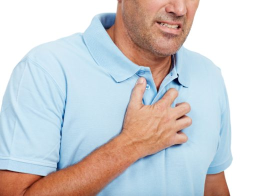 man clutching chest experiencing acid reflux